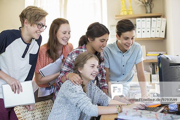 Gruppe von Teenagern  die gemeinsam den Computer im Zimmer benutzen