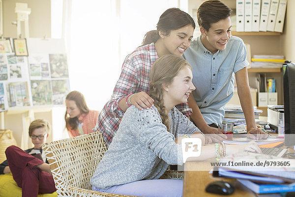 Teenager teilen sich den Computer im Wohnzimmer