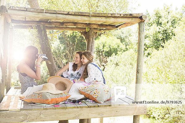 Drei Teenagermädchen fotografieren im Sommer im Baumhaus