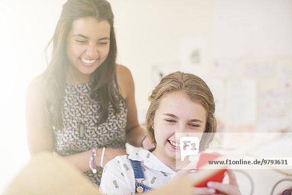 Zwei Mädchen im Teenageralter teilen sich Smartphone und lächeln