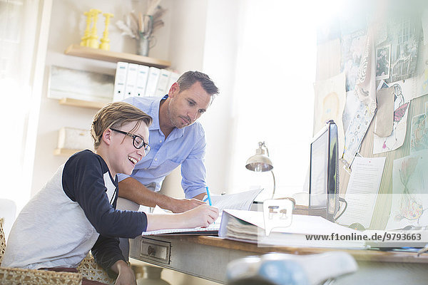 Vater hilft Teenager-Sohn bei seinen Hausaufgaben im Zimmer