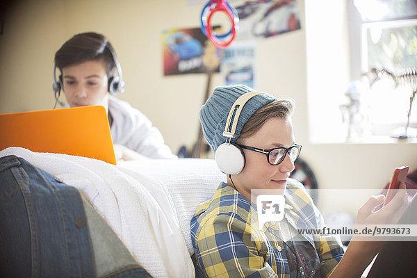 Zwei Teenager  die elektronische Geräte im Zimmer benutzen.
