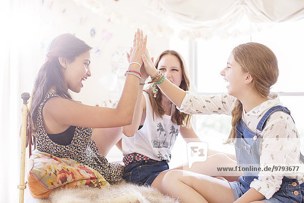 Drei Teenager-Mädchen  die High Five im Bett machen.