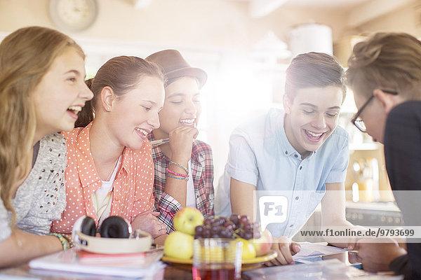 Gruppe lächelnder Teenager um den Tisch im Esszimmer versammelt