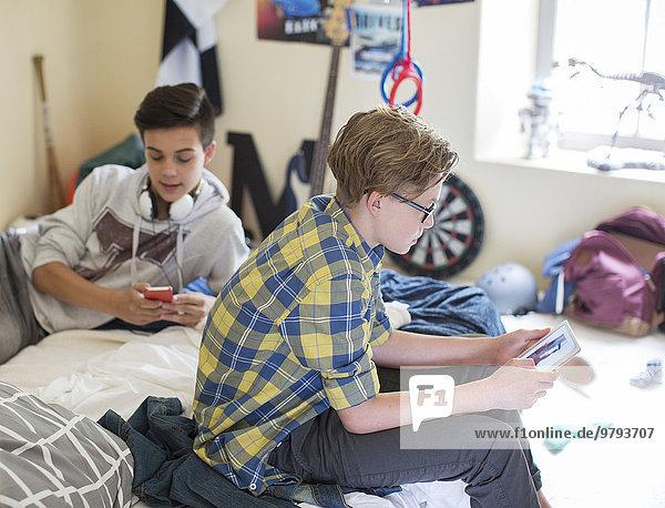 Zwei Teenager mit digitalen Geräten im Zimmer