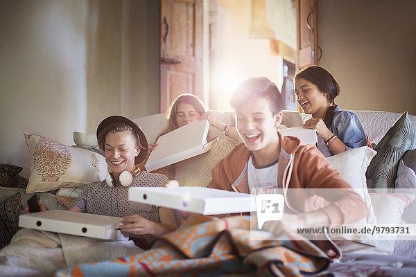 Gruppe von Teenagern öffnet Pizzakartons auf dem Sofa im Wohnzimmer