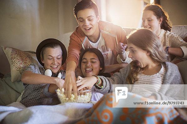 Gruppe von Teenagern essen Popcorn auf dem Sofa im Wohnzimmer