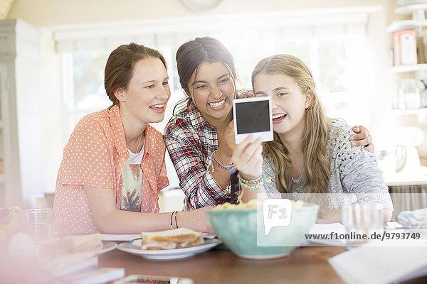 Drei Mädchen im Teenageralter  die beim Sitzen am Tisch ein Foto ansehen