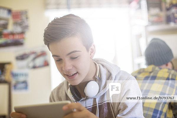 Zwei Teenager  die im Zimmer sitzen und elektronische Geräte benutzen.
