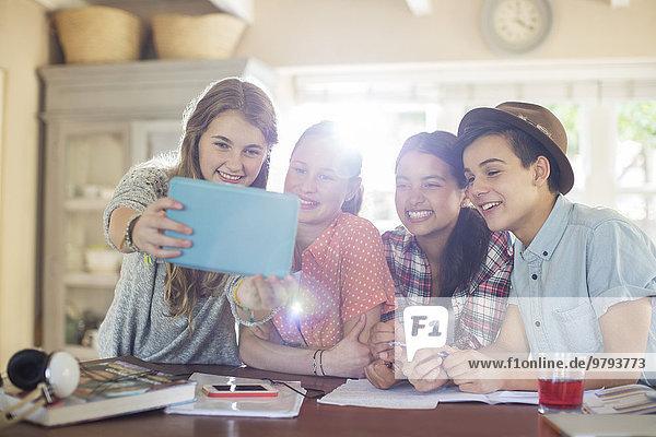 Gruppe von lächelnden Teenagern  die sich selbst im Speisesaal mitnehmen