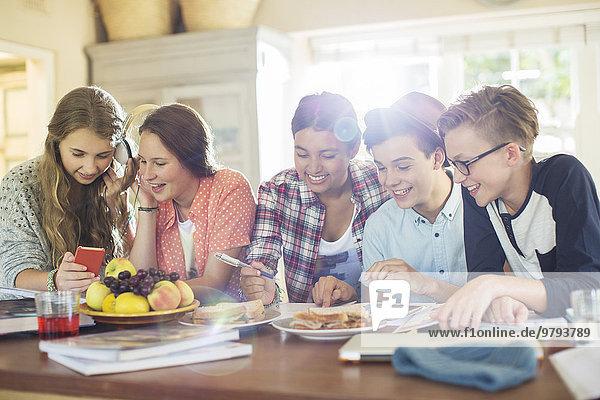Gruppe von Jugendlichen mit elektronischen Geräten am Tisch im Esszimmer