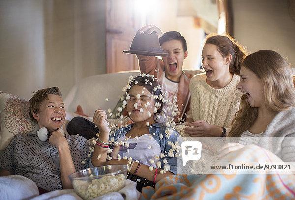 Gruppe von Jugendlichen  die Popcorn auf sich selbst werfen  während sie auf dem Sofa sitzen.