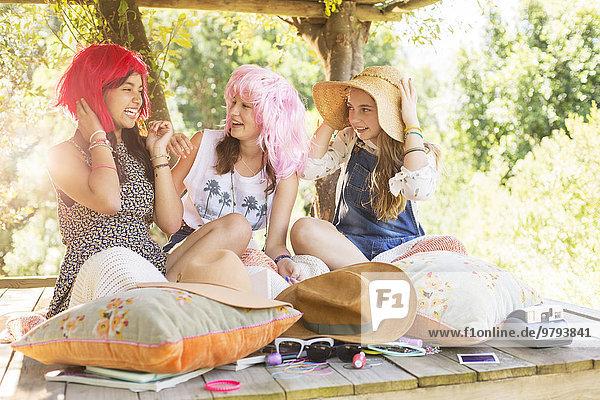 Drei Teenagermädchen mit Perücken und Hut  die im Sommer im Baumhaus sitzen.
