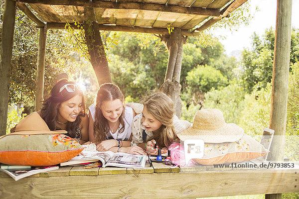 Drei Teenager-Mädchen beim Lesen im Sommer im Baumhaus