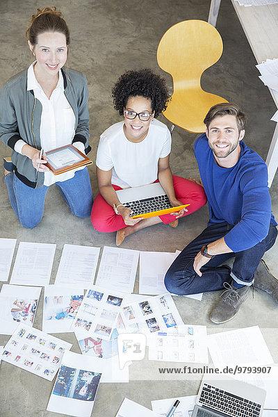 Porträt von drei Jugendlichen  die auf dem Boden sitzen und zusammen arbeiten