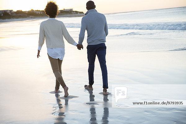 Junges Paar hält sich an den Händen und geht am Strand spazieren.