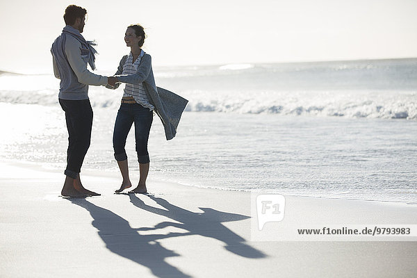 Junges Paar hält sich am Strand an den Händen