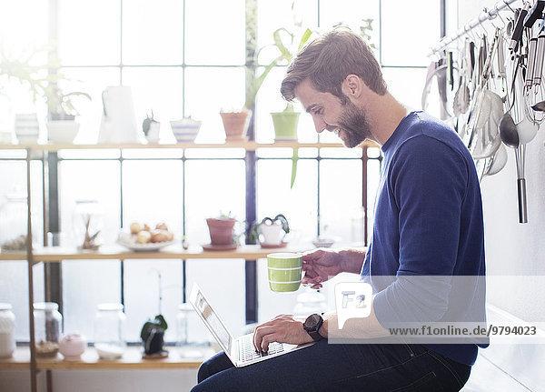 Junger Mann sitzend auf der Küchenzeile mit Becher und Laptop