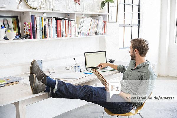 Porträt eines jungen Mannes mit Beinen auf dem Schreibtisch bei der Arbeit mit dem Laptop
