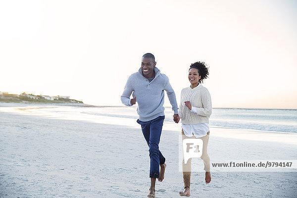 Paar hält sich an den Händen und läuft am Strand herum