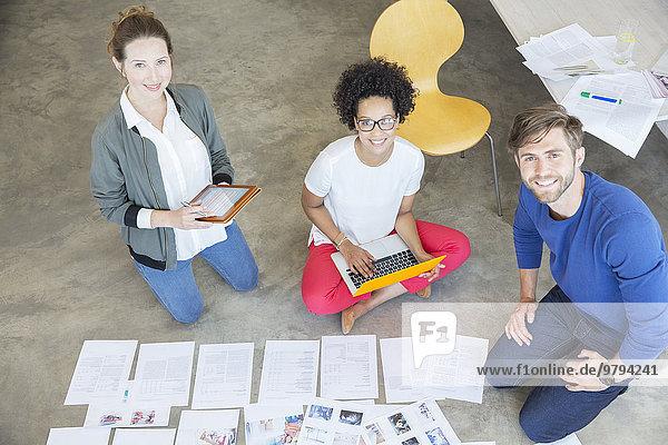 Porträt von drei Jugendlichen  die auf dem Boden sitzen und gemeinsam im Studio arbeiten