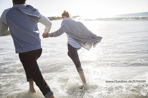 Junges Paar hält sich an den Händen und rennt am Strand.