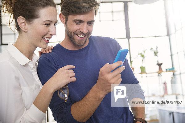 Zwei junge Leute schauen aufs Handy und lächeln