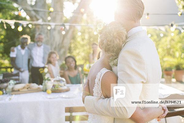 Junges Paar umarmt im Garten bei der Hochzeitsfeier