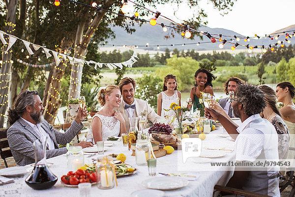 Junges Paar und seine Gäste sitzen bei der Hochzeitsfeier im Garten am Tisch