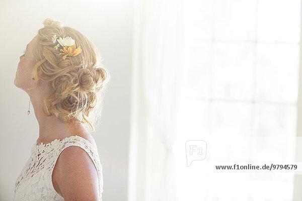 Junge Braut im sonnigen Zimmer