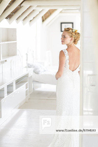 Junge Braut steht im sonnigen Schlafzimmer