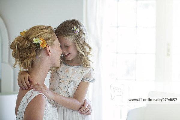 Braut und Brautjungfer stehen sich gegenüber und lächeln im Schlafzimmer.