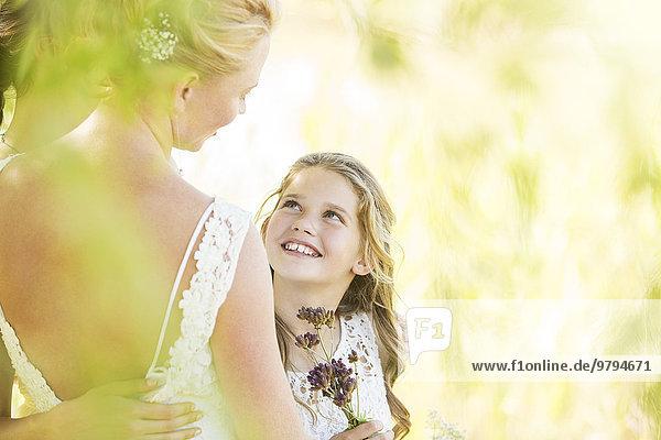 Lächelnde Brautjungfer mit Blumen und Braut bei der Hochzeitsfeier im Garten