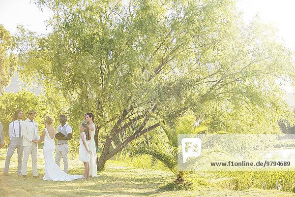 Junges Paar und seine Gäste im Garten bei der Hochzeitszeremonie