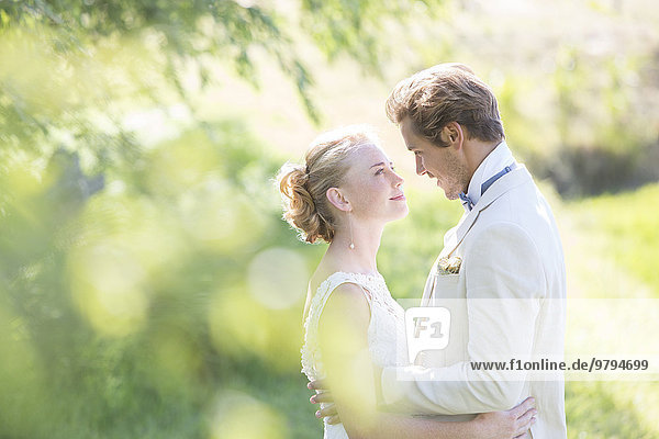 Portrait of young couple embracing in domestic garden