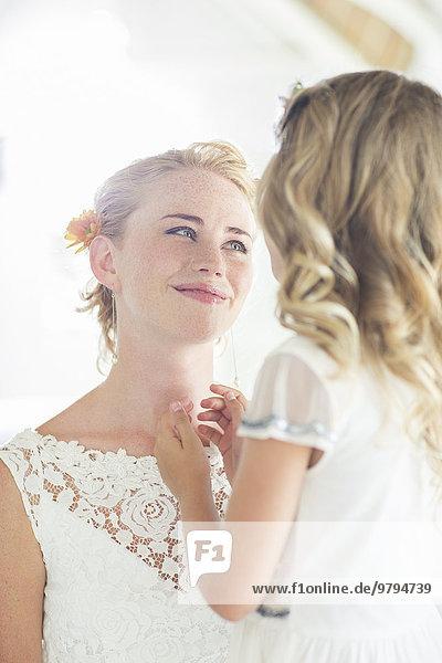 Braut und Brautjungfer einander gegenüberliegend und lächelnd
