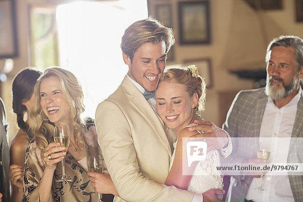 Junges Paar und Gäste bei der Hochzeitsfeier im heimischen Zimmer