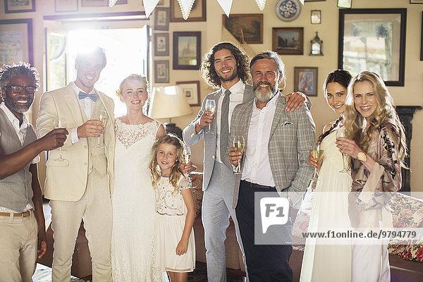 Portrait eines jungen Paares mit Gästen und Sektflöte bei der Hochzeitsfeier