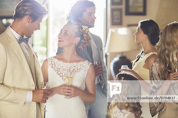Junges Paar mit Gästen und Champagnerflöten bei der Hochzeitsfeier