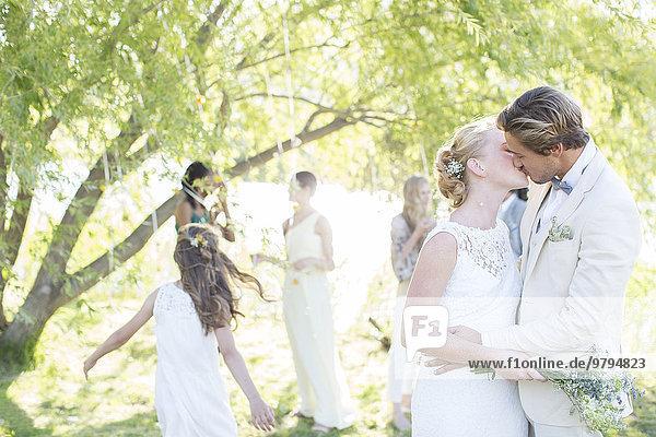 Junges Paar küsst sich bei der Hochzeitsfeier im Hausgarten