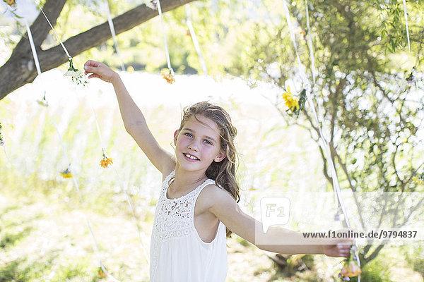 Lächelnde Brautjungfer spielt mit Dekorationen im heimischen Garten während der Hochzeitsfeier.