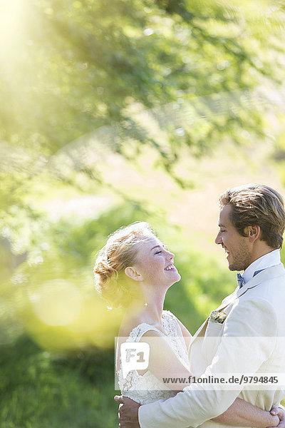 Junges lächelndes Paar  das sich im Hausgarten umarmt