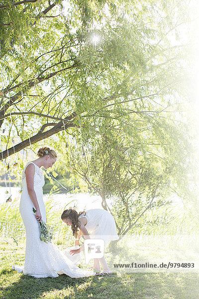 Braut und Brautjungfer stehend im Hausgarten während der Hochzeitsfeier