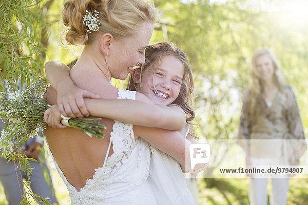 Braut umarmt Brautjungfer bei der Hochzeitsfeier im Hausgarten