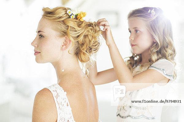 Brautjungfer helfende Braut mit Frisur im häuslichen Zimmer