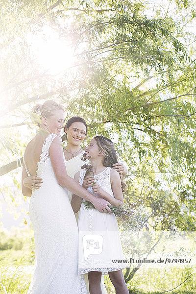 Braut und Brautjungfer im Hausgarten bei der Hochzeitsfeier