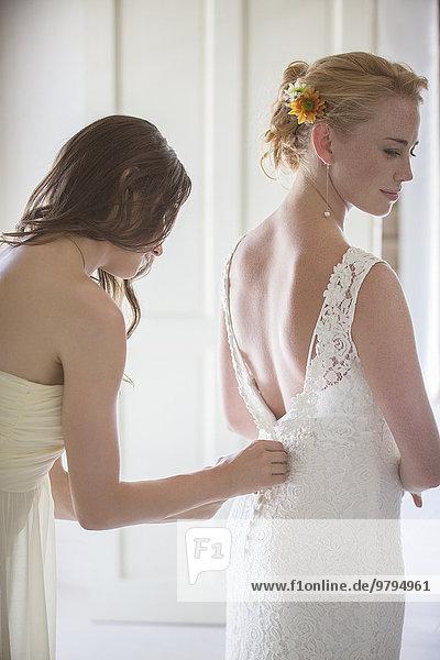 Brautjungfer helfende Braut beim Ankleiden im häuslichen Raum
