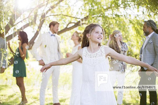 Brautjungfer spielt mit Blasen bei der Hochzeitsfeier im heimischen Garten