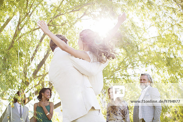 Bräutigam pflückt Brautjungfer bei der Hochzeitsfeier im Hausgarten