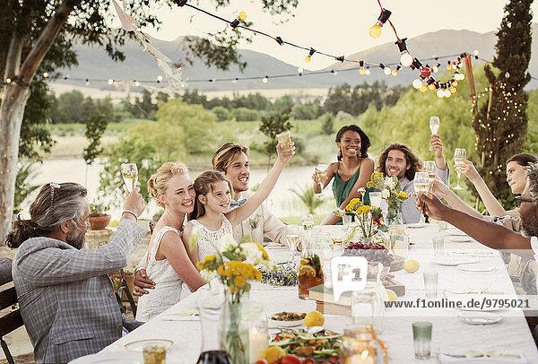 Junges Paar und Gäste toasten mit Champagner bei der Hochzeitsfeier im heimischen Garten